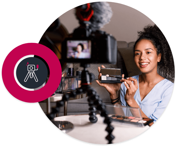Picture in a circle of a young mixed race girl making a make up video with a camera on a tripod in front of her